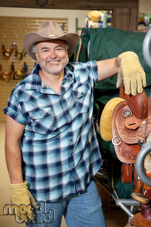 Portrait of a happy mature cowboy standing by saddle in feed store