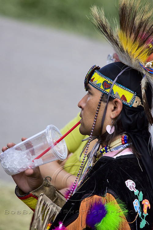 Native American male drinking from plastic cup at ceremonial Pow Wow at Browning , Montana