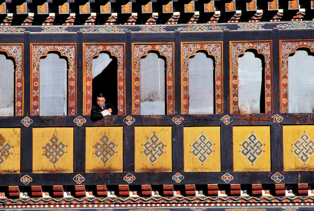A buddhist monk looks down from the beautifully decorated windows of 400 year-old Tashiccho Dzong, in Thimphu, Bhutan.