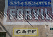 Fading business names on a village wall, on 25th May, 2017, in Homps, Languedoc-Rousillon, south of France