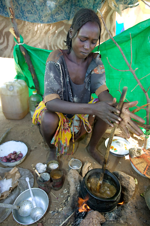 The Breidjing Refugee Camp, Eastern Chad on the Sudanese border shelters 30,000 people who have fled their homes in Darfur, Sudan. To feed her family, a woman stirs a pot of aiysh, the thick porridge that this refugee family eats three times a day. (Supporting image from the project Hungry Planet: What the World Eats.).