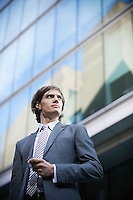 Low angle view of young businessman in suit looking away