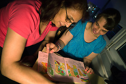 Woman Day Service Support worker looking at a story book with service user with learning disability,