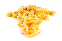 Tagliatelle raw pasta on white background