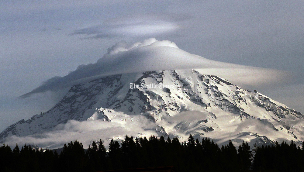 "Lenticular or ""cap clouds"" form around Mount Rainier, often signaling a change in the weather. (Alan Berner / The Seattle Times)"