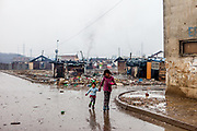 """Two children walking a street at the segregated Roma settlement """"Budulovska Street"""" (2016). In 2015 the """"muddy"""" roads to and in the settlement were asphalted and the infrastructure for the residents  improved. The city has roughly 11200 inhabitants, about 1980 (18%) of them have Roma ethnicity and around 800 are living at the segregated settlement 'Budulovska Street' (2014)."""