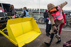 London, UK. 8 December, 2019. A climate activist from Extinction Rebellion dances in front of a mock-up of a bulldozer outside Heathrow airport during a Bikes Against Bulldozers protest against Heathrow expansion and the greenwashing of climate commitments by political parties. The protest took the form of a Critical Mass bicycle ride from Hyde Park followed by a lie-in in front of a full-scale mock-up of a bulldozer.