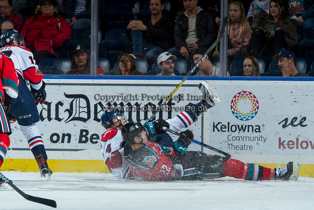 KELOWNA, CANADA - NOVEMBER 17: Braydyn Chizen #22 of the Kelowna Rockets and Tate Olson #4 of the Lethbridge Hurricanes fall to the ice after skating for the puck to the boards during first period on November 17, 2017 at Prospera Place in Kelowna, British Columbia, Canada.  (Photo by Marissa Baecker/Shoot the Breeze)  *** Local Caption ***