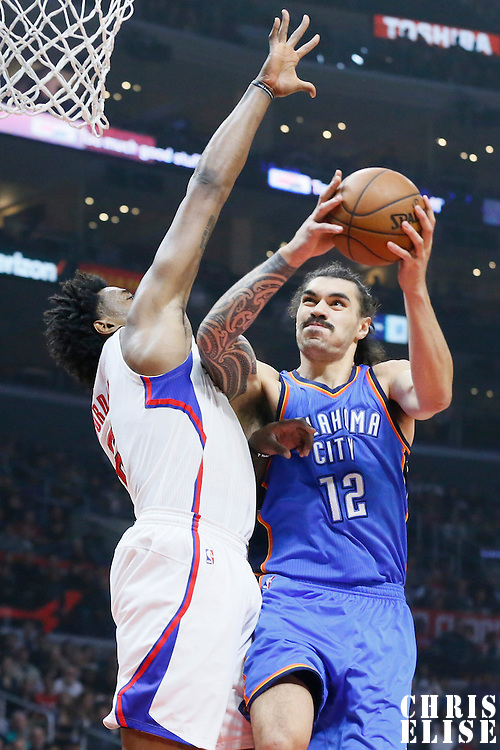 21 December 2015: Oklahoma City Thunder center Steven Adams (12) goes for the layup against Los Angeles Clippers center DeAndre Jordan (6) during the Oklahoma City Thunder 100-99 victory over the Los Angeles Clippers, at the Staples Center, Los Angeles, California, USA.