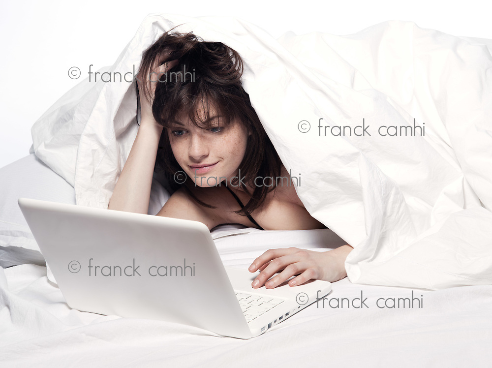 young woman in a white sheet bed on white background with a pc computer laptop
