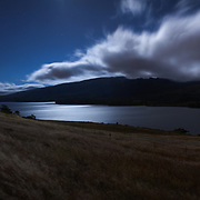 A full moon shimmers on the waters of Crystal Springs reservoir as car lights illuminate interstate 280. San Mateo County, CA.
