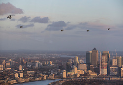 NOTE TO EDITORS - SHOT THROUGH A WINDOW, SOME REFLECTIONS ARE VISIBLE (L) © Licensed to London News Pictures. 16/01/2018. London, UK.  The last four remaining British Army Lynx helicopters are escorted by a Chinook as they fly in formation over Canary Wharf in London. The British made aircraft is being decommissioned after almost 40 years in service. Photo credit: Peter Macdiarmid/LNP