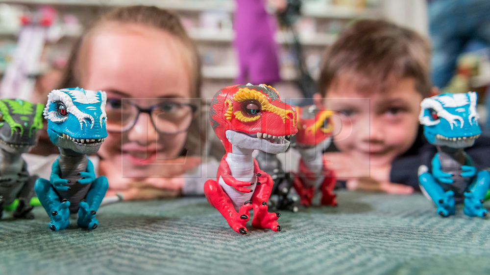 """© Licensed to London News Pictures. 14/11/2018. LONDON, UK. Allegra, aged 8, and Harry, aged 8, play with Untamed Jailbreak T-Rex Playset by Fingerlings. Preview of """"DreamToys"""", the official toys and games Christmas Preview, held at St Mary's church in Marylebone.  Recognised as the countdown to Christmas, the Toy Retailer's Association, an independent panel of leading UK toy retailers, have selected the definitive and most authoritative list of what toys will be the hottest property this Christmas. [Child models provided by show organisers, permission obtained to be photographed].  Photo credit: Stephen Chung/LNP"""