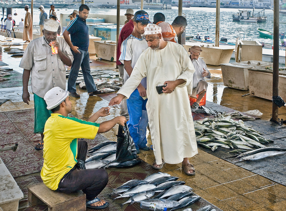 Mattrah, Muscat. Fish market with piles of fish, sellers, and buyers, in traditional Omani dress.  All are men.  One buyer hands money to a seller who in turn hands over a plastic bag of fish that he has bought.