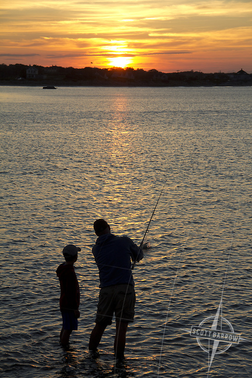 Father and son casting lesson in calm waters at sunset.