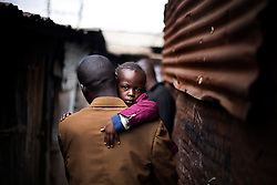 A young child is carried through the streets of Mathare, one of the poorest slums in Nairobi.  Running water and electricity are scarce and trash and human waste fills the streets.  Many people have no jobs and those who do work can earn less than one dollar a day.