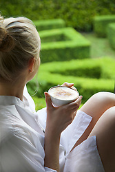 Woman Having Cappuccino Looking Out into Garden