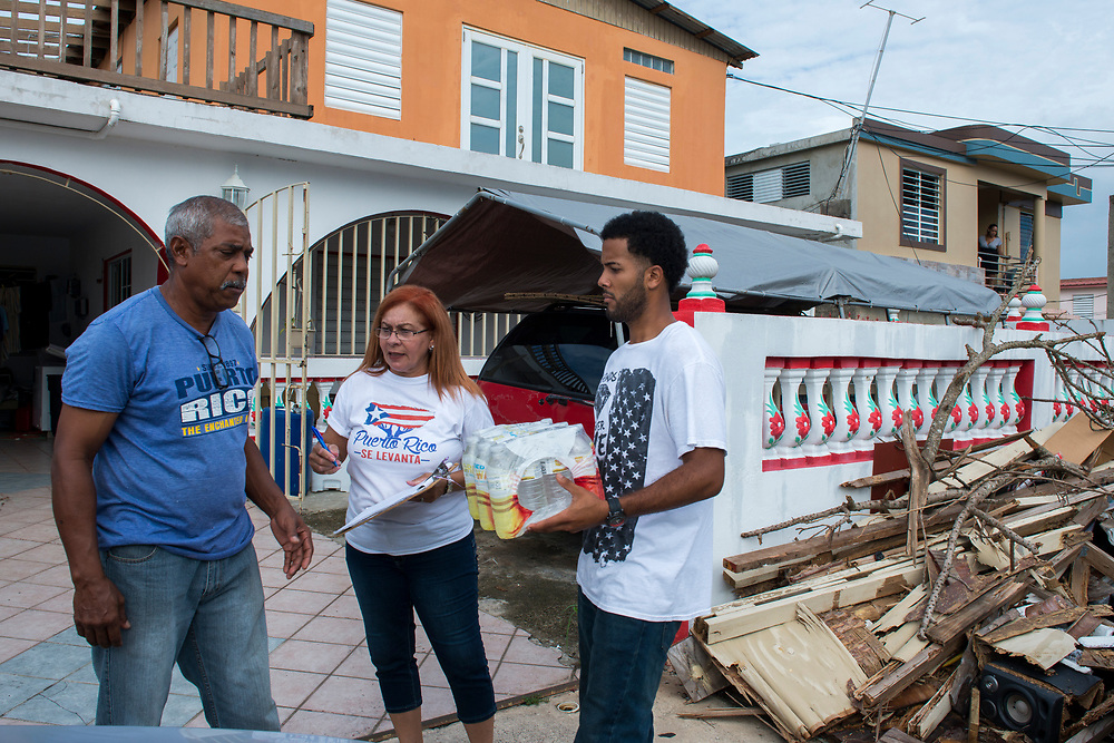 Toa Baja, PR, November 10, 2017--Inamarys Carrera, center, and Yoba D. Medina, right, are part of a team of faculty and staff of Escuela Delia Cabán who continue to distribute water and emergency relief in Tao Baja, PR neighborhoods still without power and water 50 days after Hurricane Maria.  Escuela Delia Cabán has served as a distribution point for the Puerto Rico Recovery Fund's emergency relief efforts since it was established days after the storm hit September 20, 2017.  Photo by Lori Waselchuk/BRAF