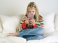 Girl sitting barefoot on sofa Playing Handheld Video Game