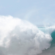A stand-up paddle boarder rides a wave at the world famous surf break, Pipeline, on the North Shore of Oahu. The late swell proved to be the last big day of the season.