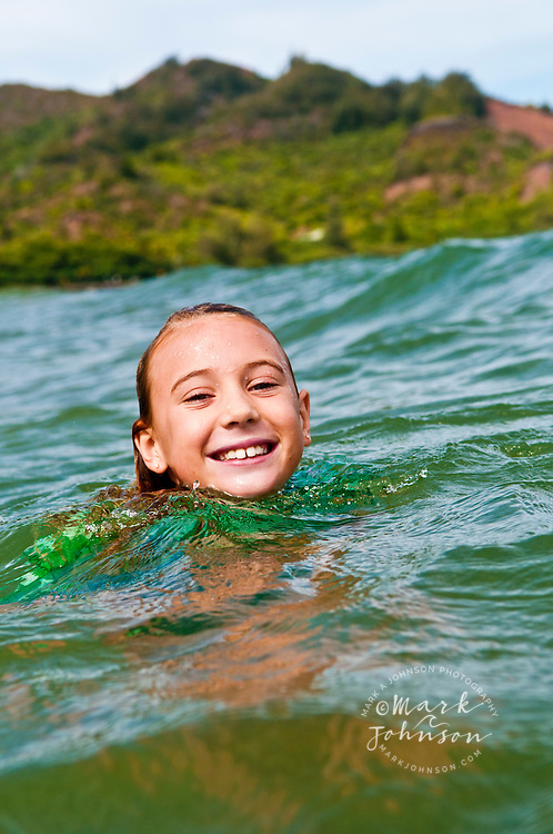 7 year old girl having fun in the ocean at Hanalei Bay, Kauai, Hawaii
