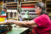 DEXTER, ME - AUGUST 4, 2015:  Cheryl Sullivan (left, 59) and Corliss Fanjoy (right, 63), employees at Erda Handbags, work together at the company's production facility in Dexter, Maine. Since most of Erda's employees are 60 years or older they have implemented a flexible scheduling system and invested in more ergonomic machines to accommodate their aging workforce. <br /> Craig Dilger for The New York Times