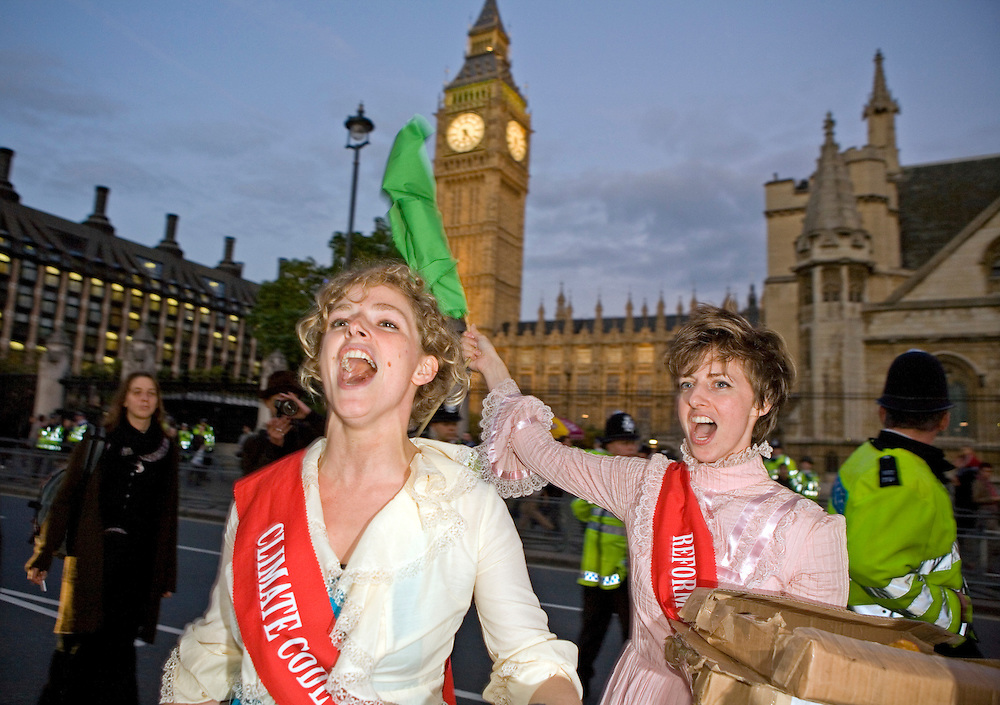 """On the 100th anniversary of the Suffragette movement Tamsin Omond lead the march into the Houses of Parliament for the Climate Rush campaign. Shouting """"Deeds Not Words"""".  Police attempted to block the path of the movement but failed until they reached the locked door at the public entrance."""