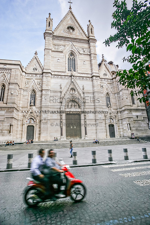 A motor scooter passes the Duomo di Napoli, or Naples Cathedral in Naples, southern Italy. The present cathedral was commissioned by King Charles I of Anjou. Construction continued during the reign of his successor, Charles II (1285-1309) and was completed in the early 14th century under Robert of Anjou.