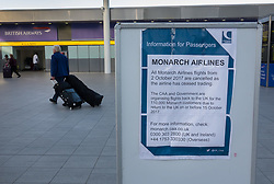 © Licensed to London News Pictures. 02/10/2017. Crawley, UK. Passengers walk past a poster at Gatwick Airport announcing that Monarch Airlines has ceased trading. The government has announced that it will start the country's biggest ever peacetime repatriation to fly about 110,000 stranded passengers home. Photo credit: Peter Macdiarmid/LNP