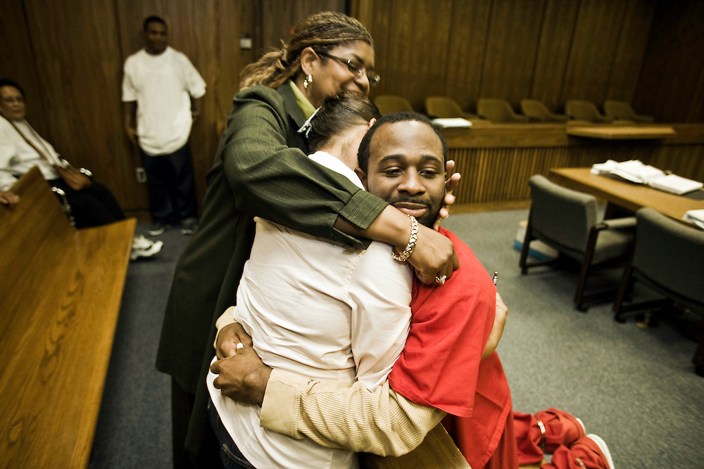 Still shackled, Daniels leans over the railing to hug his mother, Karen Daniel, and aunt, Denise Spivey after Durham Superior Court Judge Orlando Hudson had declared Daniels innocent, wrongly convicted of robbing a police department employee, for which he had been sentenced to 10 to 14 years in prison. At 22, Daniels went home for the first time since eighth grade.