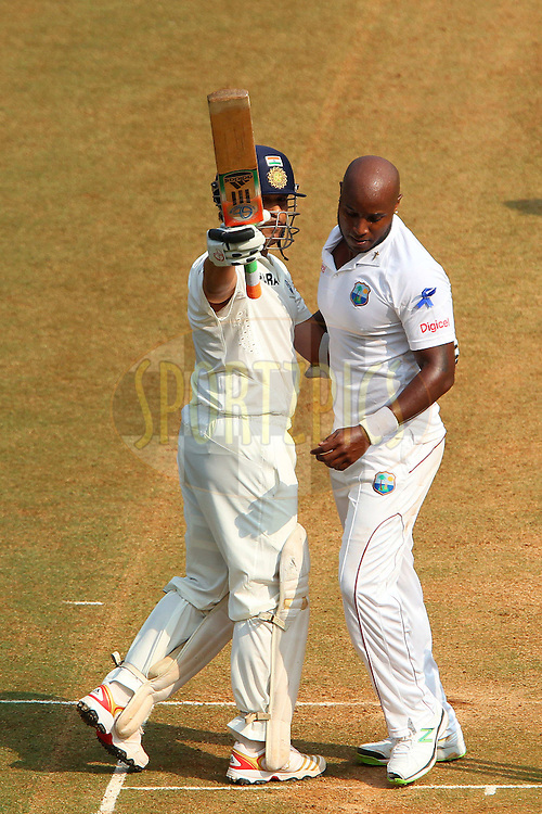 Sachin Tendulkar of India celebrates his fifty as Tino Best of West Indies walks back during day two of the second Star Sports test match between India and The West Indies held at The Wankhede Stadium in Mumbai, India on the 15th November 2013<br /> <br /> This test match is the 200th test match for Sachin Tendulkar and his last for India.  After a career spanning more than 24yrs Sachin is retiring from cricket and this test match is his last appearance on the field of play.<br /> <br /> <br /> Photo by: Ron Gaunt - BCCI - SPORTZPICS<br /> <br /> Use of this image is subject to the terms and conditions as outlined by the BCCI. These terms can be found by following this link:<br /> <br /> http://sportzpics.photoshelter.com/gallery/BCCI-Image-Terms/G0000ahUVIIEBQ84/C0000whs75.ajndY