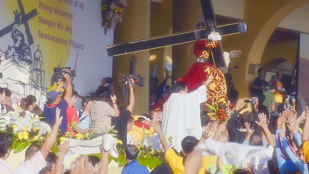 On stage with the cross and statue of the Black Nazarene as it prepares for the start of the procession to its home in Quiapo church.