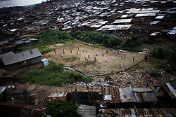 Children play soccer on a trash filled field in Mathare, one of the poorest slums in Nairobi.  Running water and electricity are scarce and trash and human waste fills the streets.  Many people have no jobs and those who do work can earn less than one dollar a day.