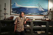 Retired NOAA employee John Chin stands in front of a map of the Mauna Loa Observatorys location at NOAA's Hilo office in Hawaii.  John Chin was a very important scientist at MLO.  For years he worked with the world-famous carbon dioxide record initiated by Dave Keeling.