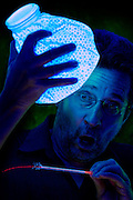 Sick man holding a glowing ice bag and reading his temperature on an exploding thermometer.Black light
