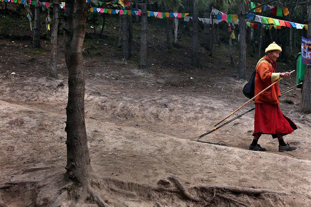 A monk descends from Nanzang Pass  as he circumambulates Kawagarbo, the third-holiest mountain in Tibetan Buddhism, Yunnan, China; September, 2013.