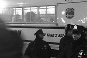 """Dec. 4, 2014 - Manhattan, NY. At the entrance to the Manhattan Bridge, NYPD officers stand guard beside a police van filled with protesters that have been arrested, while others sing protest songs and chant """"I Can't Breathe,"""" the last words of Eric Garner. 12/4/14 Photograph by Daniel Cassady/NYCity Photo Wire"""