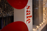A Sale sign is seen surrounded by a red theme and light bulbs in the window of a central London street.