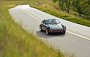 Image of a man driving a black german real 1973 Porsche 911 RS Carrera on a country road near Paso Robles, California, model and property released
