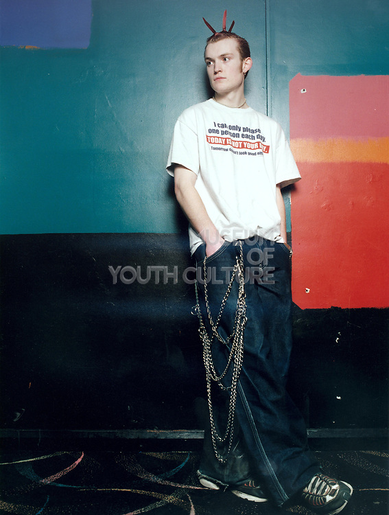 Young male punk rocker standing with hands in pockets.