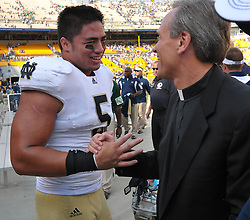 Linebacker Manti Te'o (5) is congratulated by Notre Dame President Rev. John Jenkins, C.S.C. after defeating Pitt.
