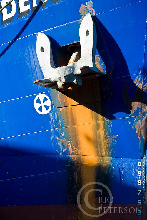 cargo ship anchor against bright blue hull