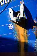 cargo ship anchor against bright blue hull