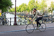In Amsterdam rijdt een man al bellend door de binnenstad op een racefiets.<br /> <br /> In Amsterdam, a man drives while phoning through the city on a road bike.