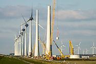 Nederland, Urk, 29 feb 2016<br /> Windpark in het IJsselmeer voor Urk. Het windpark is op de laatste paar windmolens na klaar. Ook op het land komt een lange rij grote windmolens, totaal komen er 86 turbines. Daarmee is dit het grootste windpark van Nederland met een productie van 1,4 miljard KWh per jaar.<br /> <br /> Foto (c) Michiel Wijnbergh
