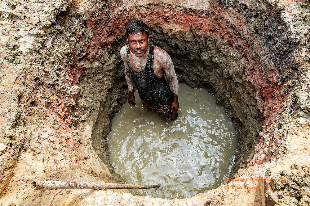 Working in Circles:  A young man, covered in mud, takes a break from toiling in the bottom of a deep, round, water filled hole in Dhaka Bangladesh. The hole is surprisingly circular and has cut through numerous layers of coloured clay.