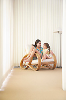 Teenage girl (16-18) sitting on armchair with sister (5-6)