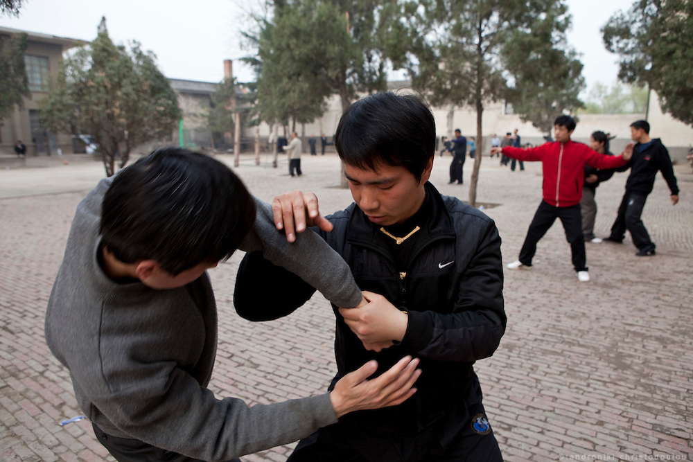 Teacher Chen Hui showing pushing hands techniques to students which are trainning outdoors at  the Taijiquan school in Chenjiagou village. Most students of the school live at the dormitories and rooms of the school untill they complete their studies.