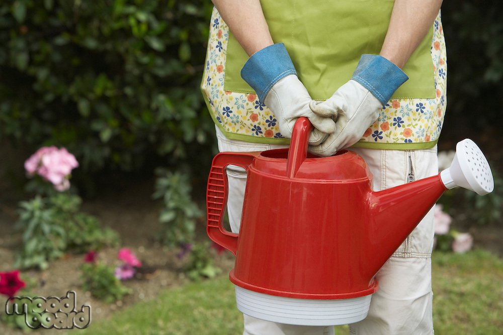 Woman holding watering can in garden, mid section