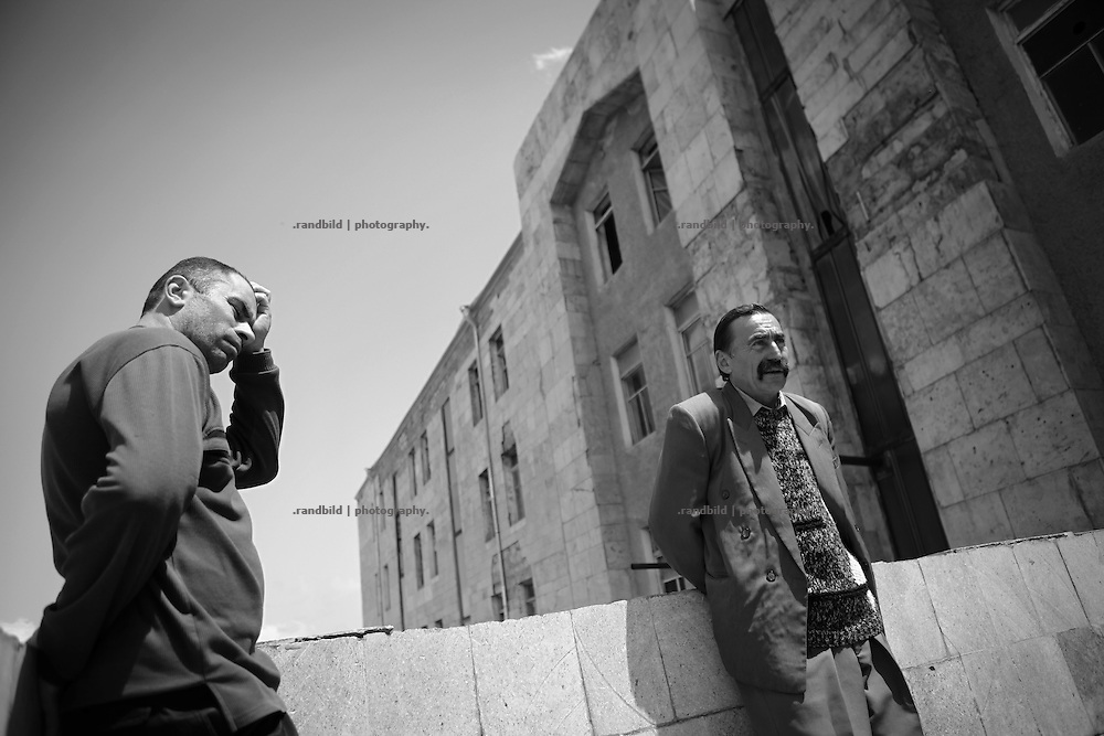 "Two men waiting in front of the post office to receive their weekly salary. But the armored car didn´t arrive this friday without any notice why. This image is part of the photoproject ""The Twentieth Spring"", a portrait of caucasian town Shushi 20 years after its so called ""Liberation"" by armenian fighters. In its more than two centuries old history Shushi was ruled by different powers like armeniens, persians, russian or aseris. In 1991 a fierce battle for Karabakhs independence from Azerbaijan began. During the breakdown of Sowjet Union armenians didn´t want to stay within the Republic of Azerbaijan anymore. 1992 armenians manage to takeover ""ancient armenian Shushi"" and pushed out remained aseris forces which had operate a rocket base there. Since then Shushi became an ""armenian town"" again. Today, 20 yeras after statement of Karabakhs independence Shushi tries to find it´s opportunities for it´s future. The less populated town is still affected by devastation and ruins by it´s violent history. Life is mostly a daily struggle for the inhabitants to get expenses covered, caused by a lack of jobs and almost no perspective for a sustainable economic development. Shushi depends on donations by diaspora armenians. On the other hand those donations have made it possible to rebuild a cultural centre, recover new asphalt roads and other infrastructure. 20 years after Shushis fall into armenian hands Babies get born and people won´t never be under aseris rule again. The bloody early 1990´s civil war has moved into the trenches of the frontline 20 kilometer away from Shushi where it stuck since 1994. The karabakh conflict is still not solved and could turn to an open war every day. Nonetheless life goes on on the south caucasian rocky tip above mountainious region of Karabakh where Shushi enthrones ever since centuries."